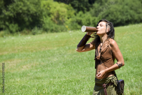 Fotografia beautiful young viking woman drinks thirstily from a bottle of mead