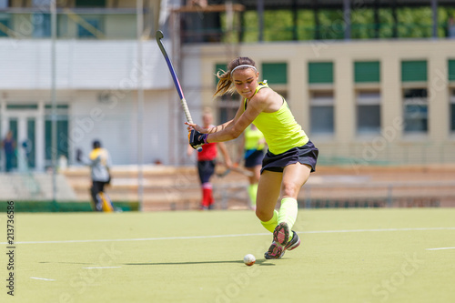 Young hockey player hit the ball in field hockey game