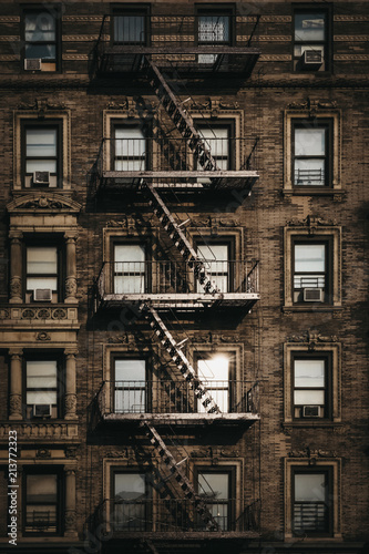 Photo Facade of a typical New York block of flats with fire escape at the front, sun reflects in the windows
