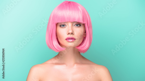 Fotografia confident young woman with pink bob cut looking at camera isolated on turquoise