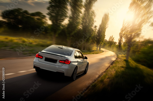 Fotografia White car is driving on empty countryside asphalt road at sunset