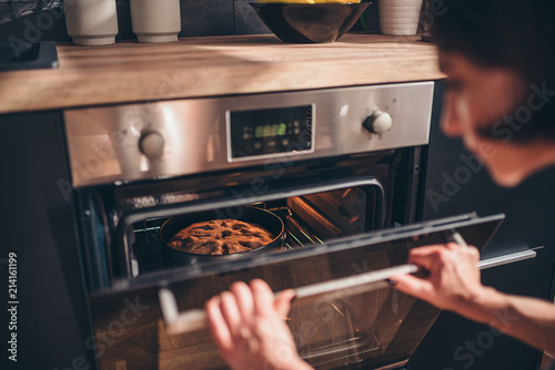 Tablou Canvas Woman checking apple pie in oven