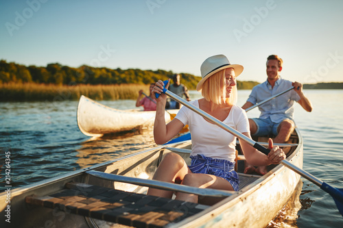 Fotografía Laughing young woman canoeing on a lake with friends
