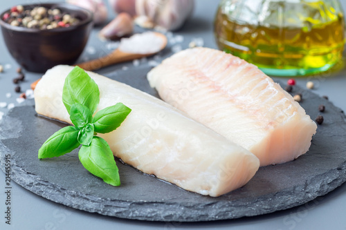 Fresh raw cod fillet with spices, pepper, salt, basil on stone plate, horizontal