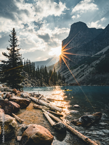 Fotografia Sunrise with turquoise waters of the Moraine lake with sin lit rocky mountains in Banff National Park of Canada in Valley of the ten peaks