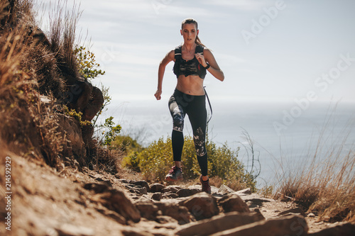 Fototapeta Woman running over rock trail on mountain