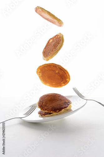 Flying stack of pancakes with blueberry, blackberry and raspberry isolated on white background