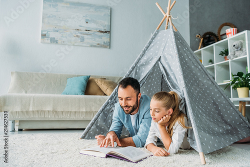 Obraz na płótnie father and daughter lying on floor inside of teepee and reading book together at