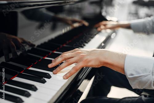 Obraz na plátně Male pianist hands on grand piano keyboard