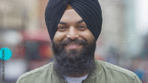 Fotografie, Obraz Portrait of smiling Indian male in a turban looking to camera on a street