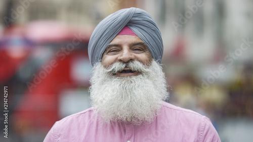 Fotografie, Obraz Portrait of senior Indian man in a turban smiling to camera on the street