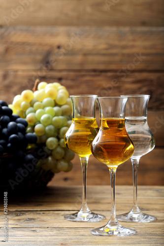 Canvas Print grappa disitllato di uva in tre bicchieri di vetro sfondo rustico