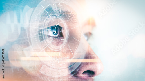 The double exposure image of the businessman looking up during sunrise overlay with cityscape image and futuristic hologram. The concept of modern life, technology, iris scanner and internet of things