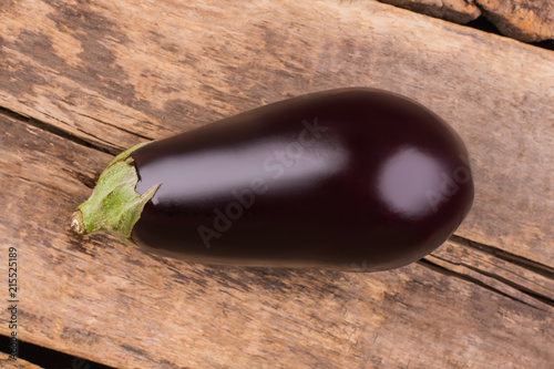 Raw aubergine on a wooden background. Top view. Ready for cooking.