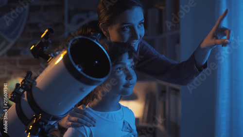 Cute sisters watching the stars with a telescope