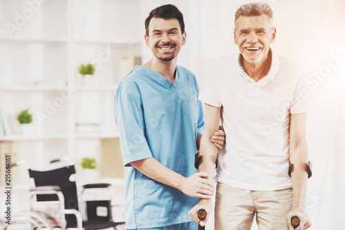 Tableau sur Toile Smiling Doctor Helps Old Man Patient with Crutches