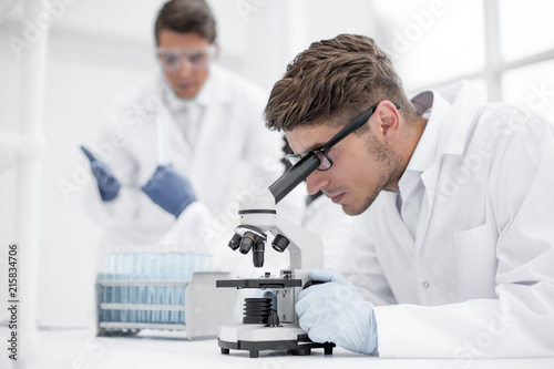 close up.the scientist looks through the microscope