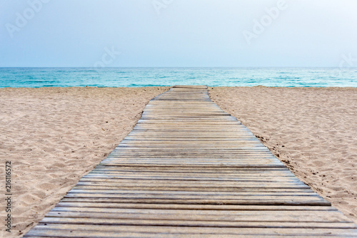 Fotografia Wooden boardwalk at beach in sand and sea in the background