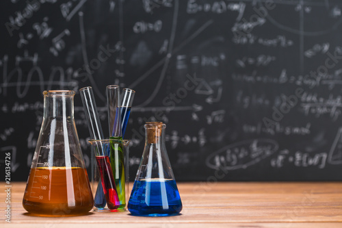 Canvas Print Tubes with chemical liquids stand on a wooden table on a chalkboard background