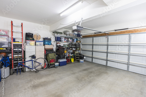 Photo Organized suburban residential garage with shelves, file cabinets, tools and sports equipment