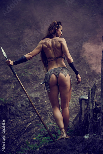 Fotografia, Obraz Beautiful Amazonian girl in chain mail with a spear in the woods