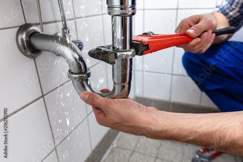 Slika na platnu Plumber Repairing Sink Pipe Leakage