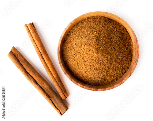 Fotografia Cinnamon sticks and wooden plate with ground cinnamon on a white