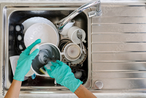 Young woman with gloves washing dishes in the kitchen