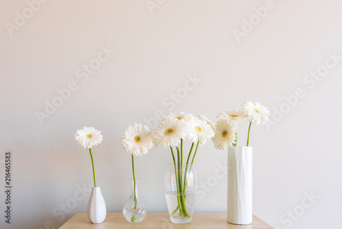 White gerberas in four glass and ceramic vases on wooden shelf against neutral wall background