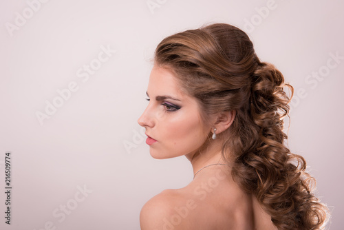 Brown-haired woman with professional hair and make-up against a light background close-up.