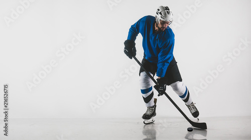 Portrait of Caucasian male ice hockey player in uniform performing a wrist shot against white background