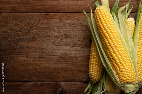 Fresh corn on cobs on rustic wooden table, closeup Fotobehang