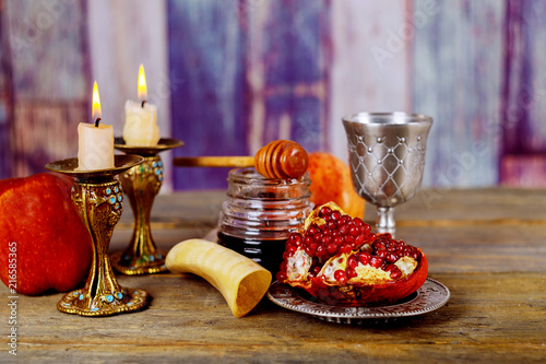 Honey, apple and pomegranate on wooden table over bokeh background