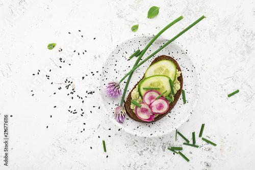 Valokuva Toast avocado puree, cucumber, onion, onion flowers, radish and daikon on slices of dark bread on a light background with sesame seeds