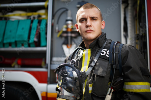 Canvas Print Photo of young firefighter standing near fire truck with fire hose