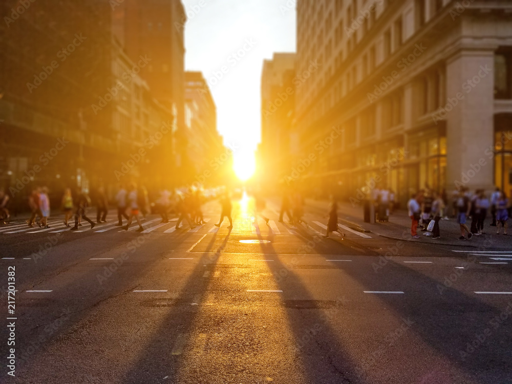 Group of anonymous people walk across the street on 5th Avenue in Manhattan New York City with sunlight setting in the background