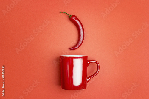 Red coffee mug with chili peppers on a red background. The concept of a hot drink