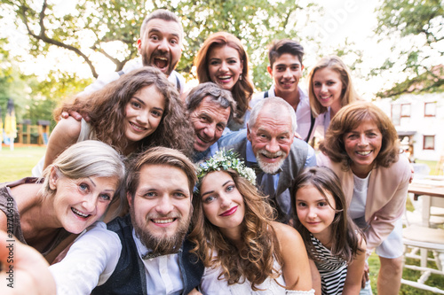 Bride, groom with guests taking selfie at wedding reception outside in the backyard Fototapet