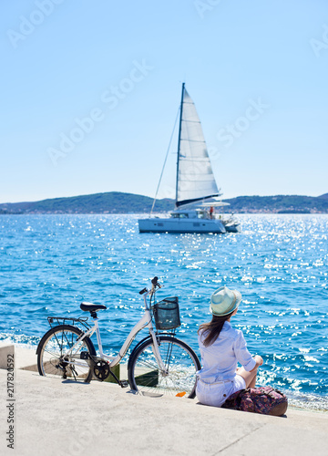 Back view of tourist woman in sunglasses with backpack sitting at bicycle on paved sidewalk under clear blue sky watching sailing ship in azure sea water. Perfect summer landscape on bright sunny day