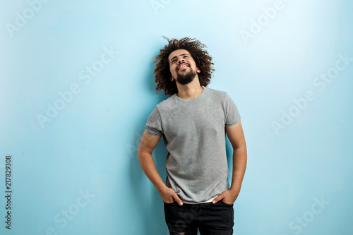 A curly-headed handsome man wearing a gray T-shirt and ripped jeans is standing and smiling with his hands in the pockets, looking upwards over the blue background Fototapeta