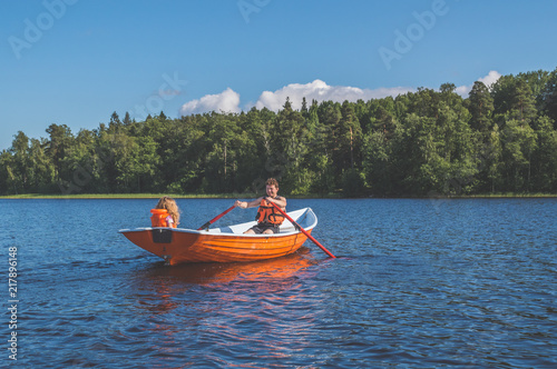 Fotografia man and the child, the girl in the boat, rowing on the lake