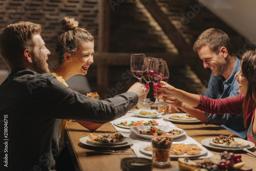 Tableau sur Toile Friends making celebratory toast at dinner table