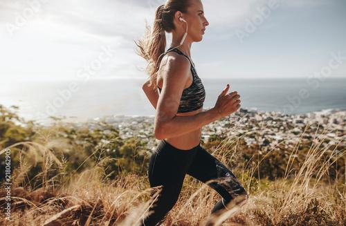 Fit woman running through mountain trail