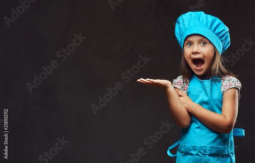Surprised little girl dressed in blue cook posing in a studio. Isolated on dark textured background.