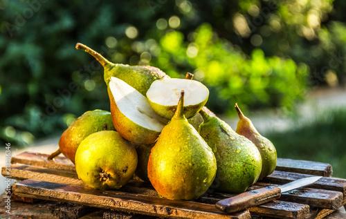 Juicy fresh pears on an old wooden board. Juicy ripe pears in a sunny garden. Harvesting. Garden fruits