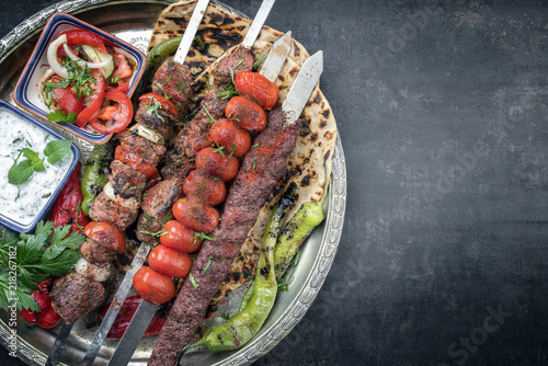 Traditional oriental Adana kebap and shashlik skewer with tomato and flatbread as top view on a plate with copy space right