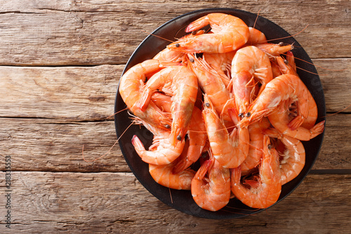 Healthy diet food: boiled wild tiger shrimps close-up on a plate on a table. Horizontal top view
