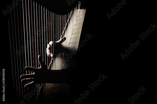 Photo Harp player. Hands playing Irish harp strings