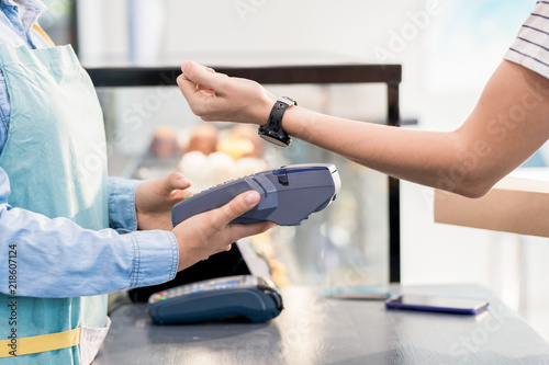 Side view mid section of unrecognizable woman paying by smart watch via NFC for her order in shop or cafe