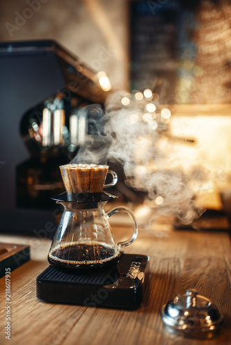 Glass coffee pot with steam on wooden counter Fototapet